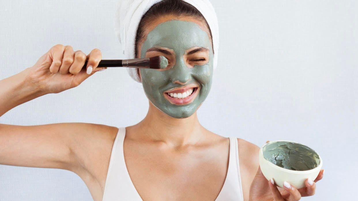 Lady applying green mask to face