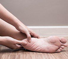 hands holding heel of feet