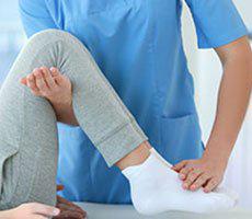 Doctor bending knee of patient