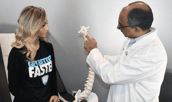 Dr. Sharan holding plastic spine to explain to female patient