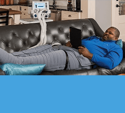 man on couch with compression leggings and machine