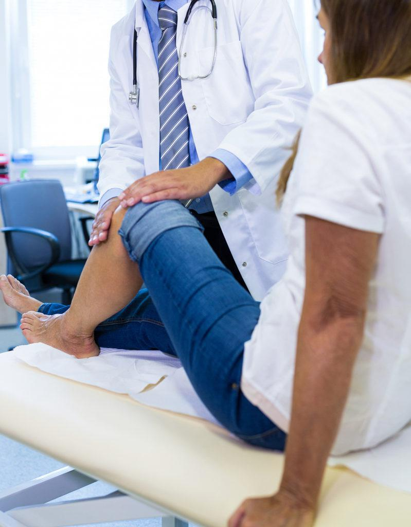 Woman holding knee at doctor's office
