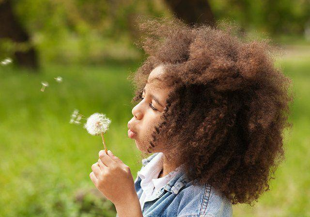 Girl blowing a flower