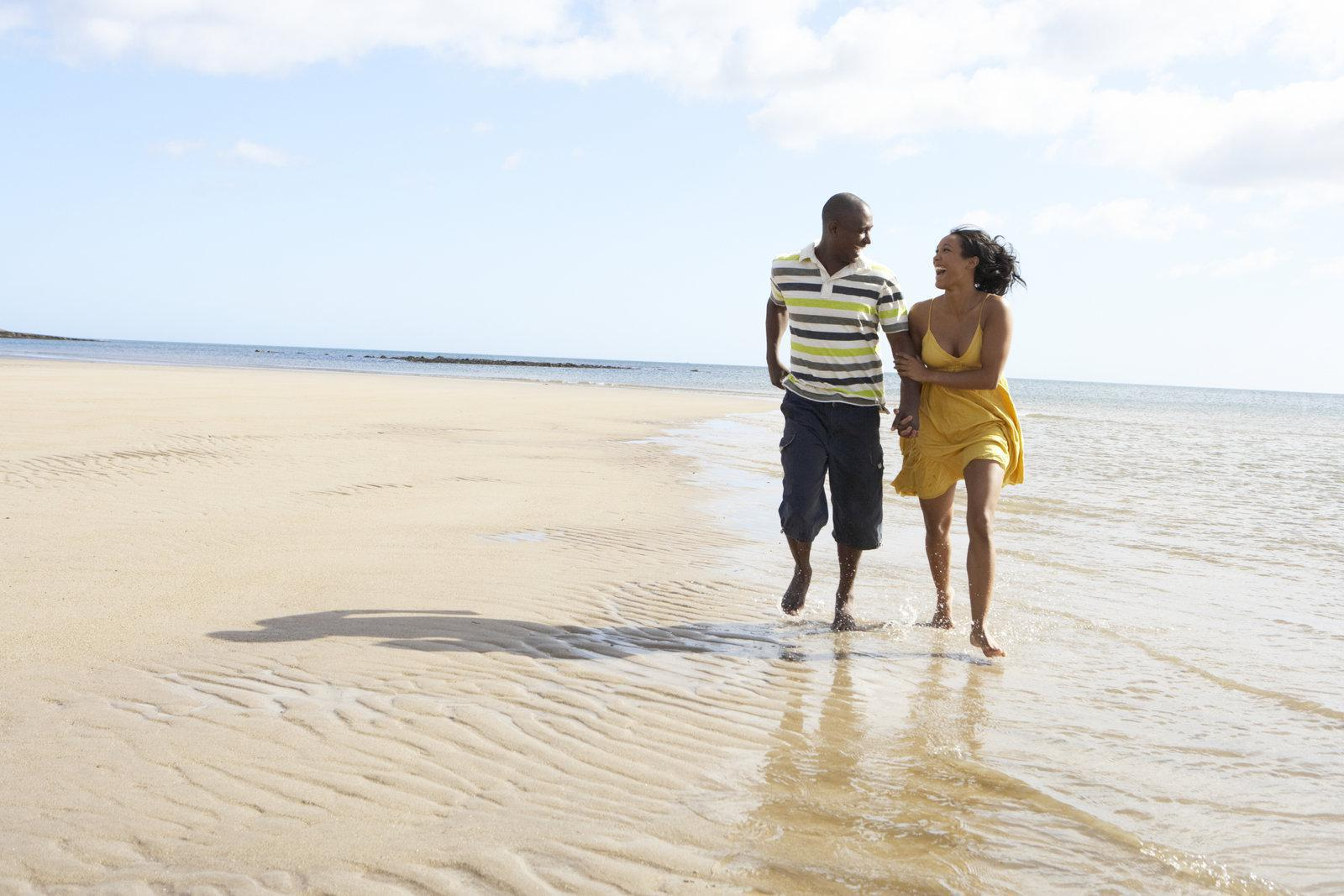 African-American couple walk on a Northwest Florida beach holding hands in summertime.
