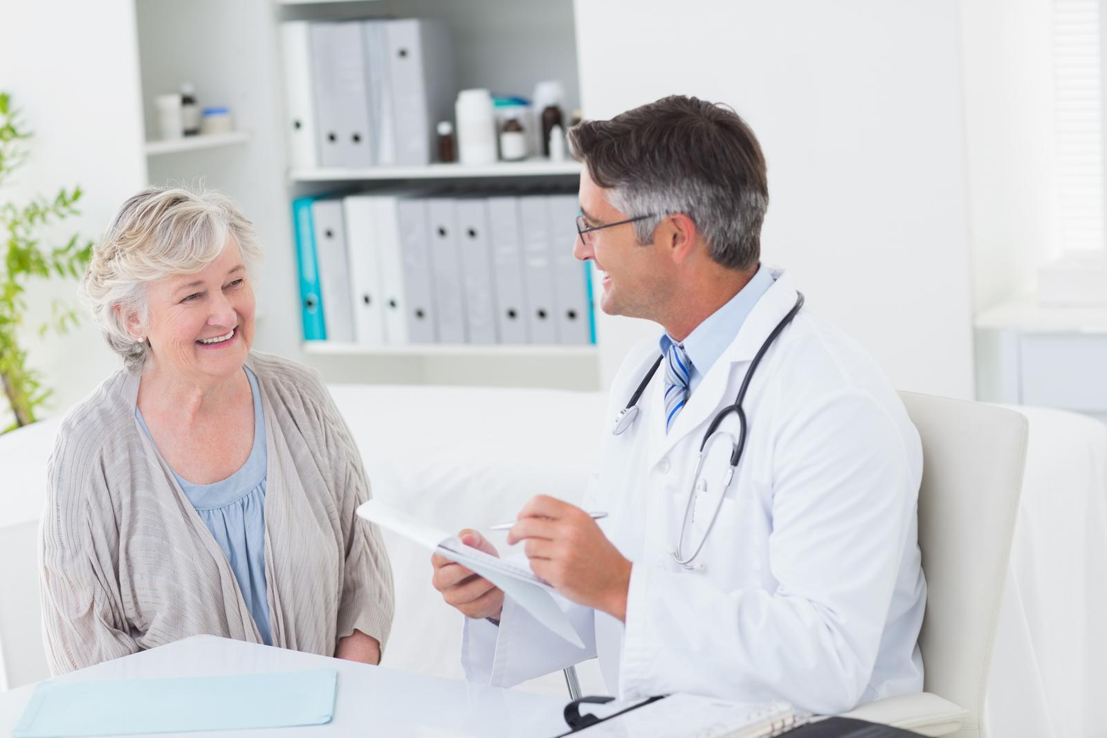 A cannabis physician consults with a smiling elderly woman patient in a medical marijuana clinic.