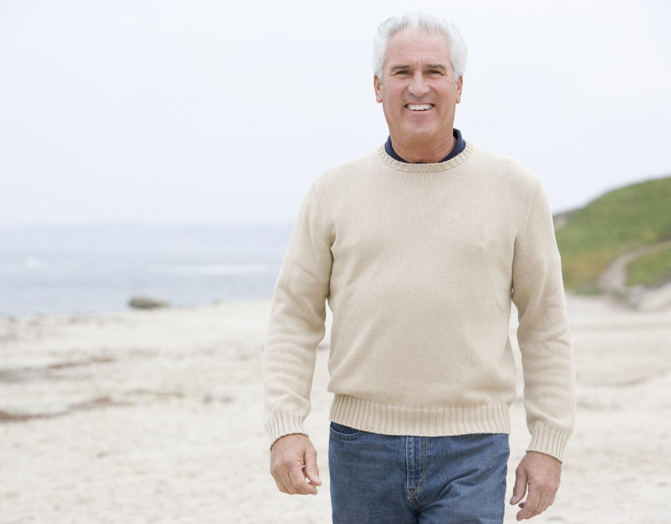 Relaxed and handsome older man walking on the beach in a sweater.