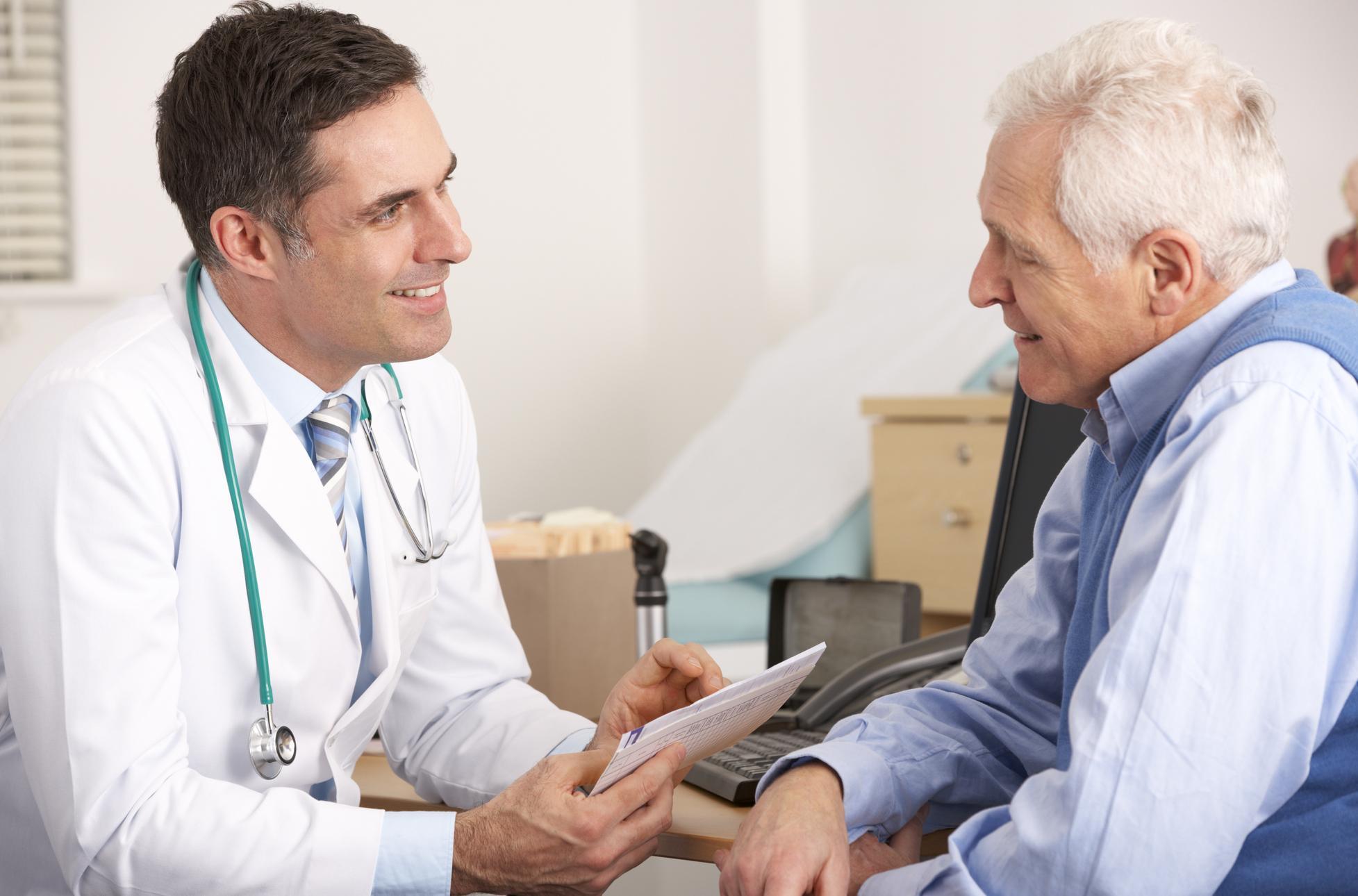 Smiling marijuana doctor talking to an older man.