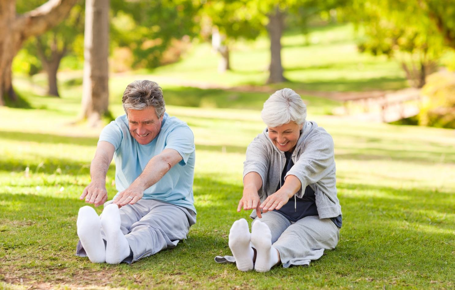 An older couple sitting on the grass in the park doing stretches.