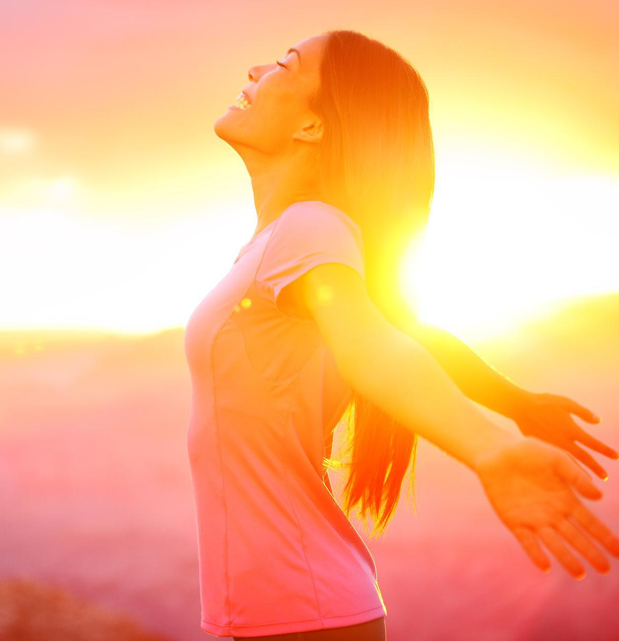 A woman shows a happy and relaxed expression with arms outstretched, on the beach at sunset.