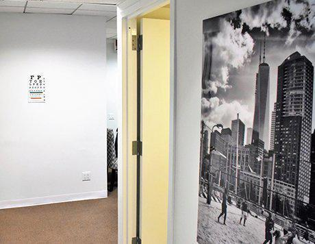 Office hallway with black & white picture of New York City, with an open door ahead and an eye exam chart.