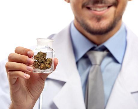 physician holding a small bottle of marijuana