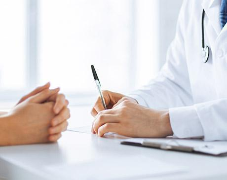 physician and patient's hands discussing