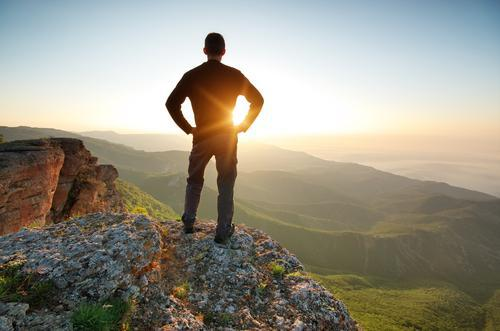 man standing on mountain watching sunset