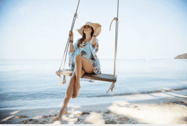 Girl on swing on beach