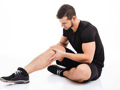 Athletic man holding his knee