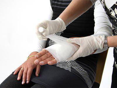 nurse wrapping hand in gauze