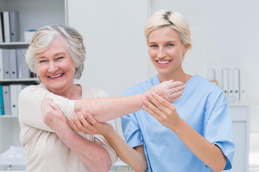 elderly woman and her nurse smiling