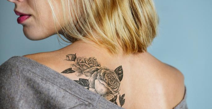 woman looking at tattoo on her shoulder