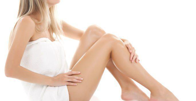 woman in towel touching legs