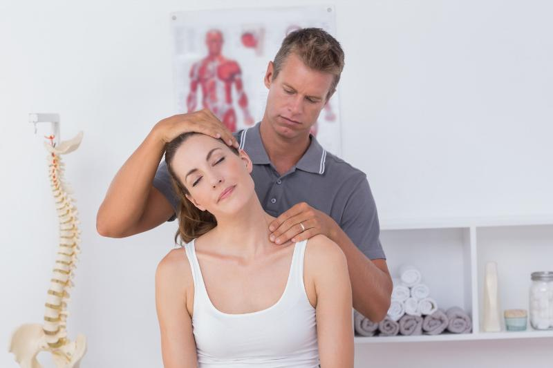 Chiropractor adjusting a woman's neck.