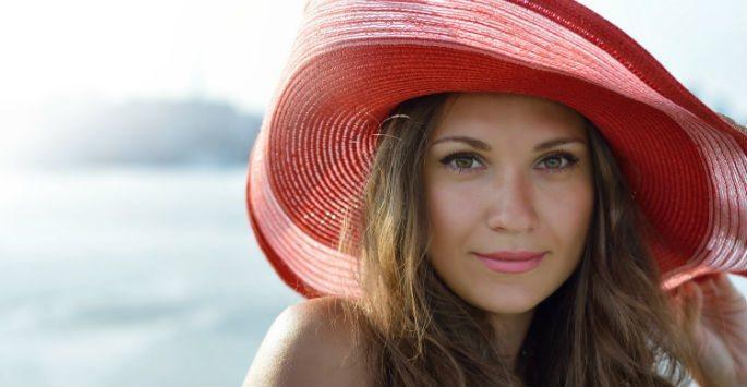 woman wearing hat by the ocean