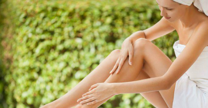 woman in towel touching legs