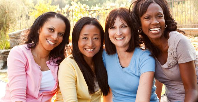 women grouped together and smiling