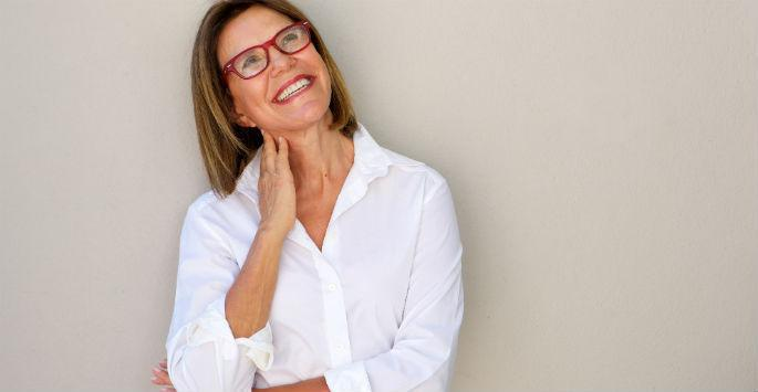 woman in glasses smiling against wall