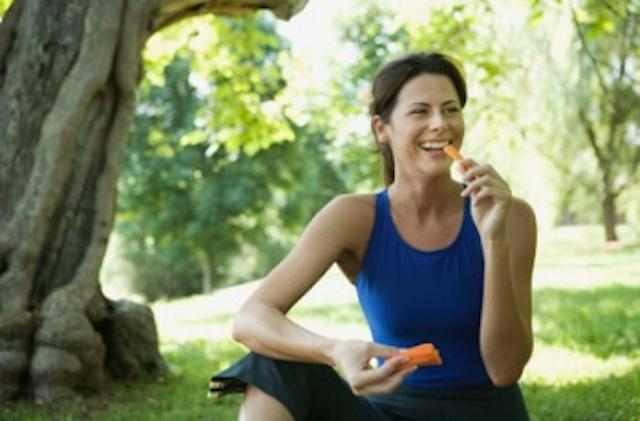 woman sitting in park eating carrots
