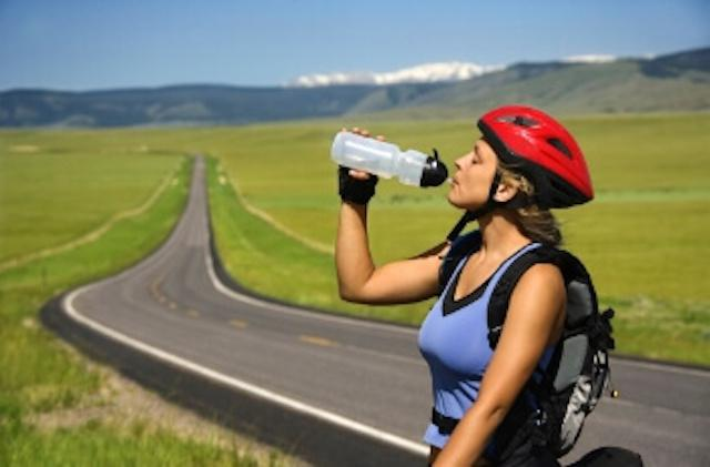 woman riding a bike drinking water