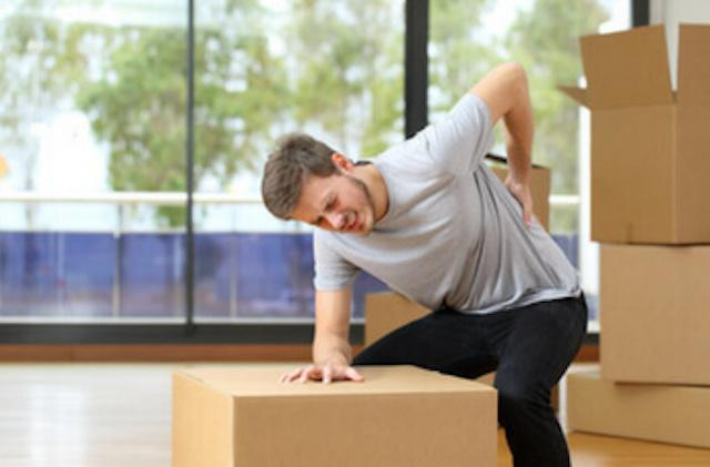 man moving boxes with back pain