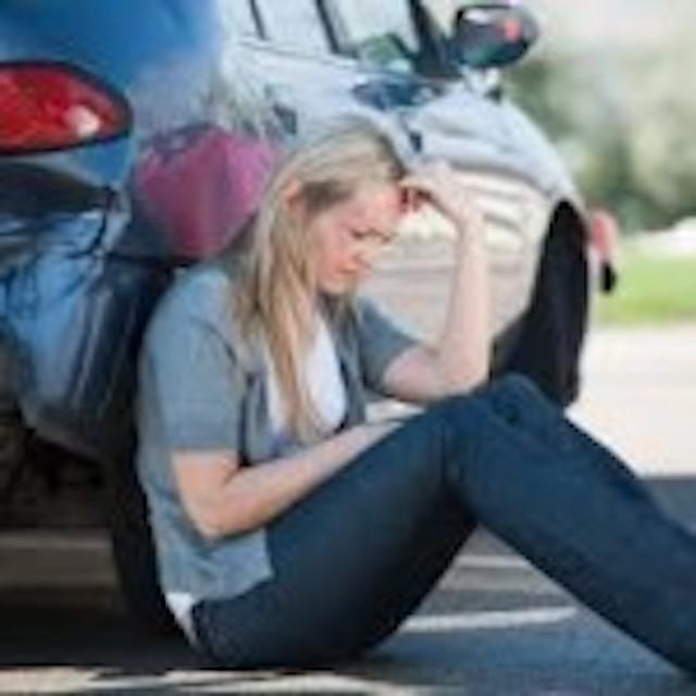 woman leaning against car looking sad