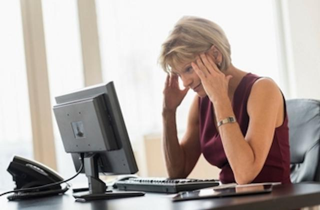 woman hunched over computer with headache