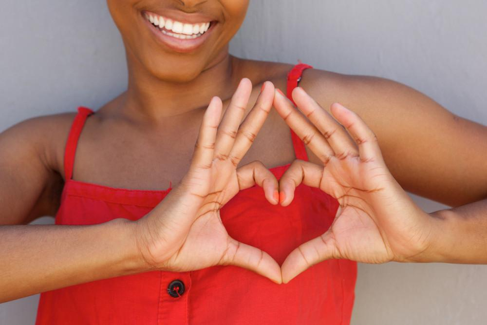 February is American Heart Month. Woman holding up a heart to chest,