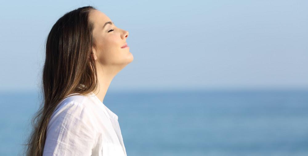 Woman enjoying a deep breath of fresh ocean air