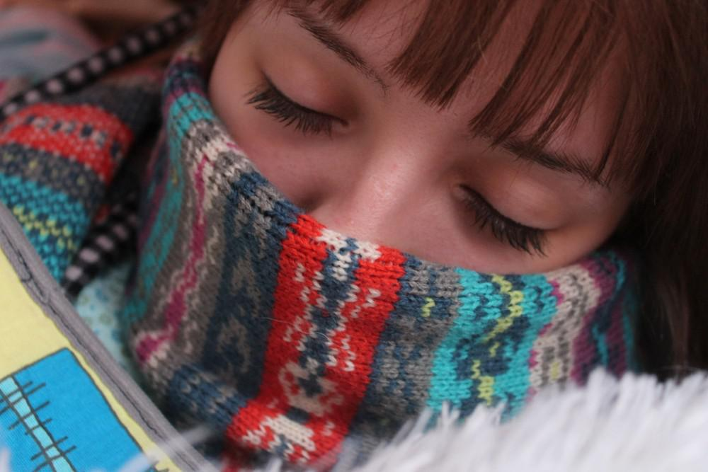 Girl with eyes closed wearing scarf.