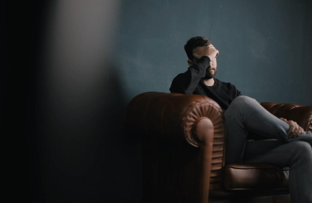 guy on couch with headache