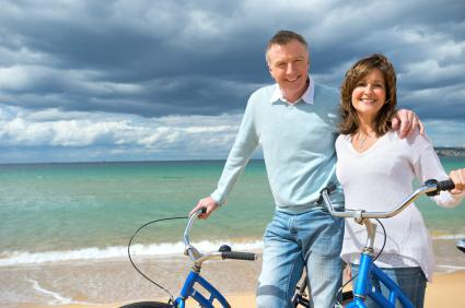 Two people smiling riding bikes on the beach