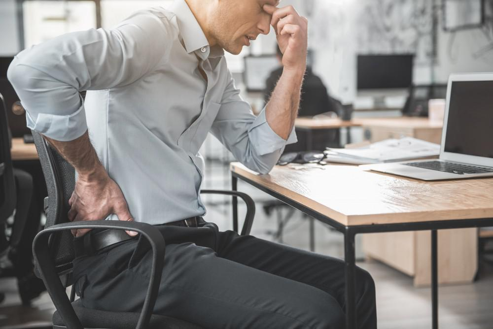 Sitting properly at your desk will help your posture