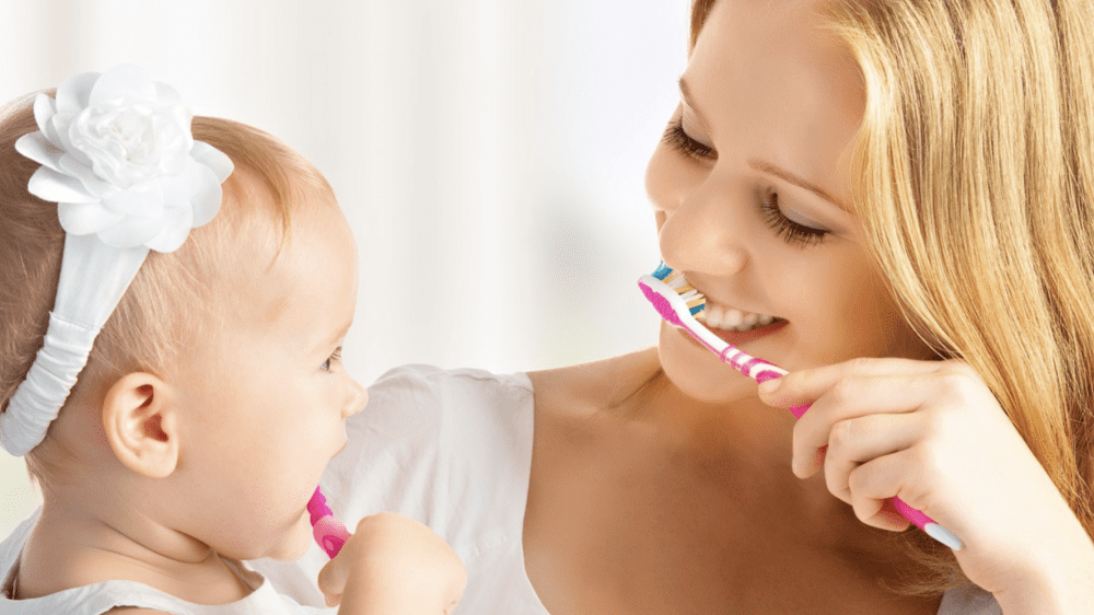 Woman and baby brushing teeth