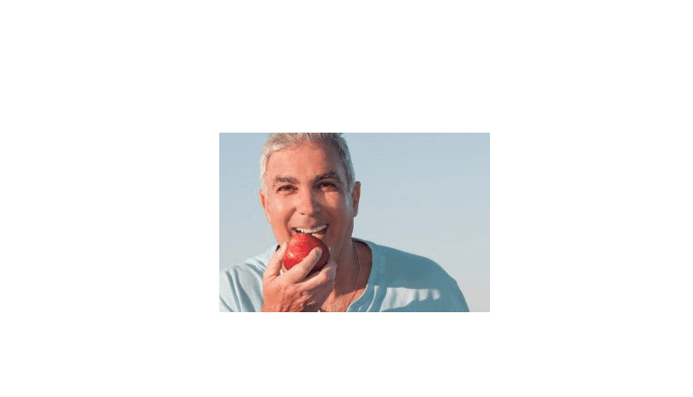 A smiling man eating an apple.