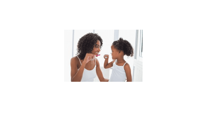 A woman brushing her teeth with her daughter.