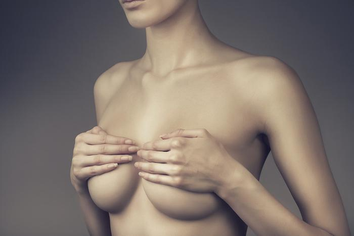 woman covering breast with hands