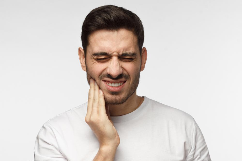 Man holding his jaw with his face twisted in pain