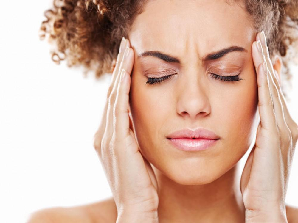 Woman rubbing her temples from headache or TMJ pain