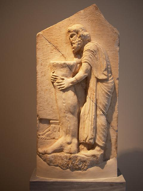 Greek Relief Sculpture of a Man holding a leg