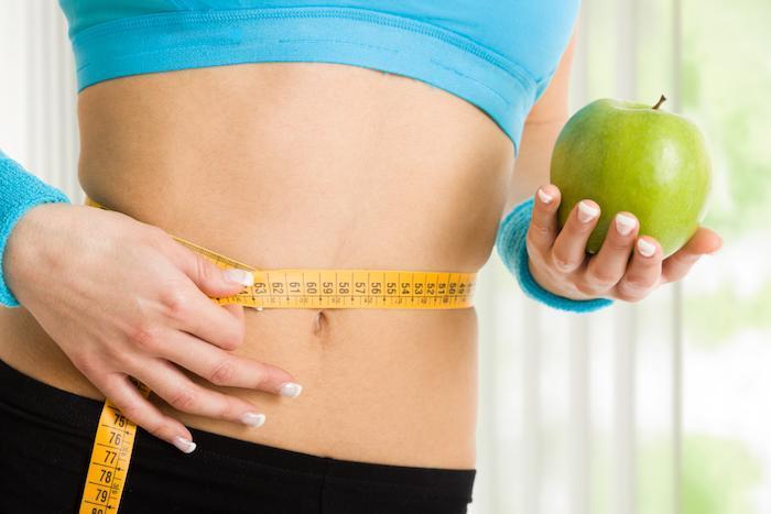 measuring tape around woman's waist, holding an apple