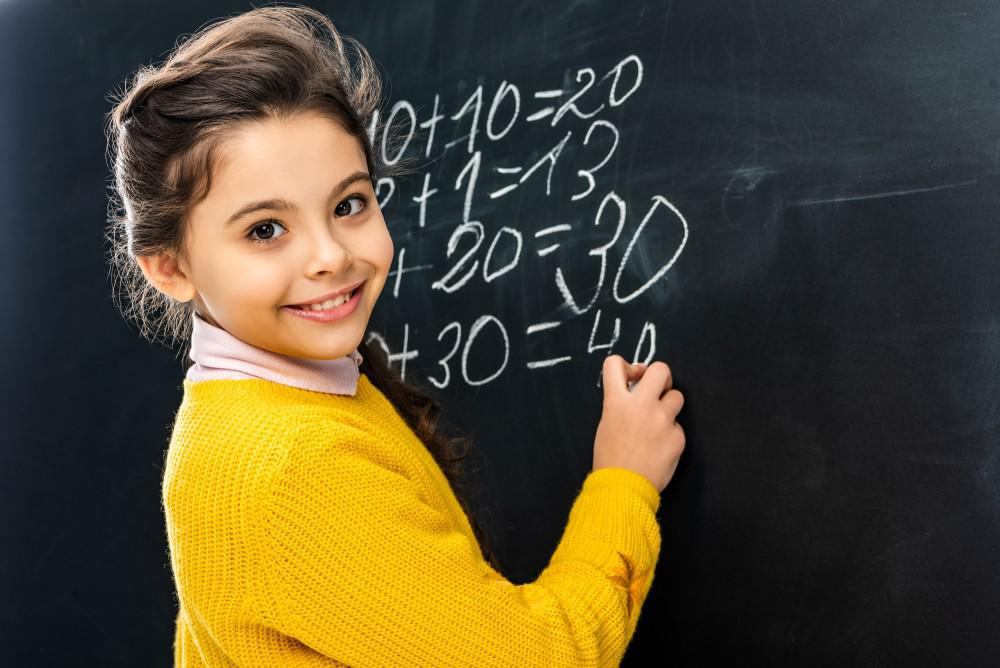 Child doing math on a chalkboard