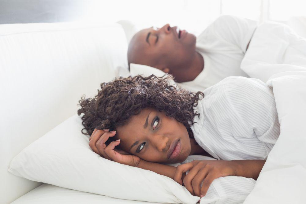 woman in bed awake from snoring