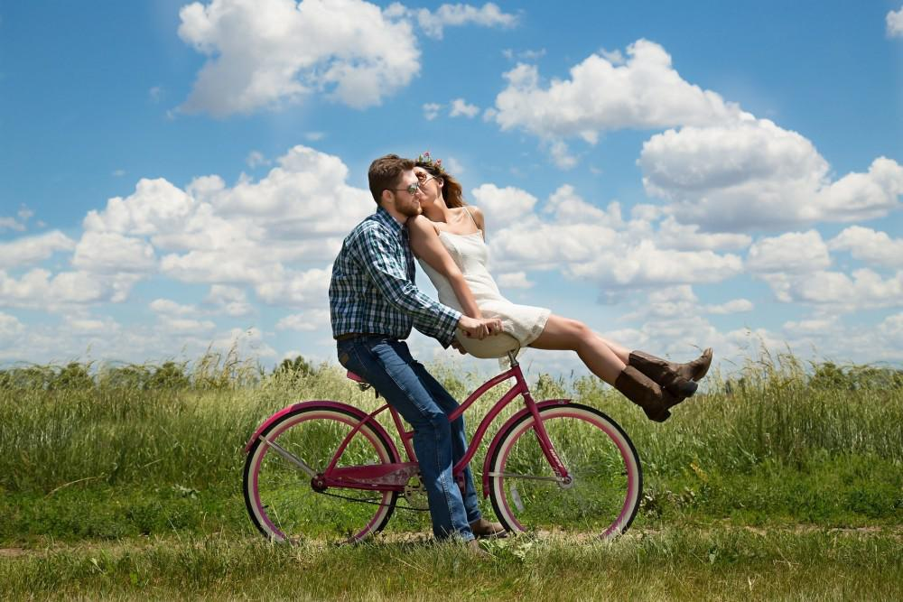 Couple on bike with clouds